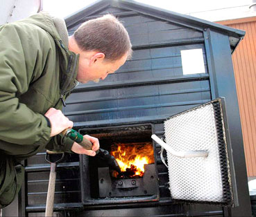 Dave Pederson adds fuel to a biomass pellet stove | Photo by West Central Tribune