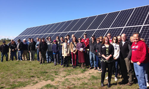 Tour participants gathered for a big group photo in front of Detroit Lake's Community Solar Garden
