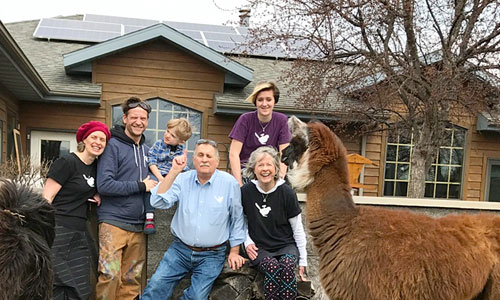 Ron and Kathy Gray, front right, along with (left to right) their daughter Miranda, son-in-law Scott, and grandchildren Murdock and Gwendolyn, pose with their rooftop solar energy system. Llamas from their family business join in the fun.
