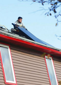 A worker for All Energy Solar carefully placed a panel onto the roof of the Art House B&B. It took the company about two days to install the panels