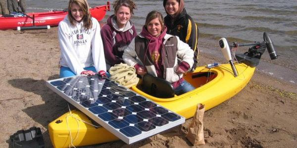Four young women clustered in and around a kayak with a solar panel attached.