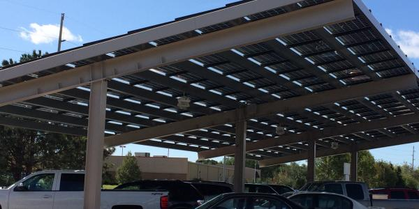 Cars parked under a solar panel-covered shelter in Red Wing