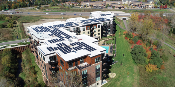 aerial view of apartment building with solar panels on roof; Photo credit: Impact Power Solutions