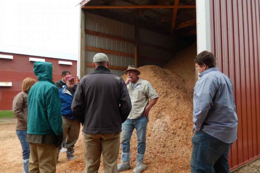 Viking Company owner Bill Koenig of Albany, MN shows tour participants the wood fuel storage bunker containing two types of fuel used in the biomass heating system for one of his broiler chicken barns.