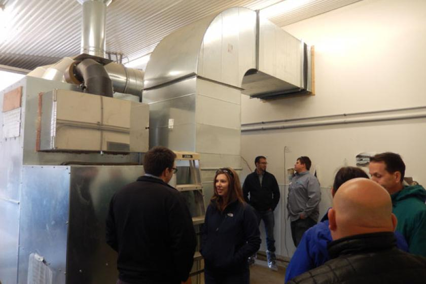 Tour participants take a close look at the biomass furnace heating a barn at Viking Company, a broiler chicken growing operation in Albany, MN.