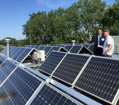 Mayor Peter Lindstrom shows off solar panels atop Falcon Heights City Hall